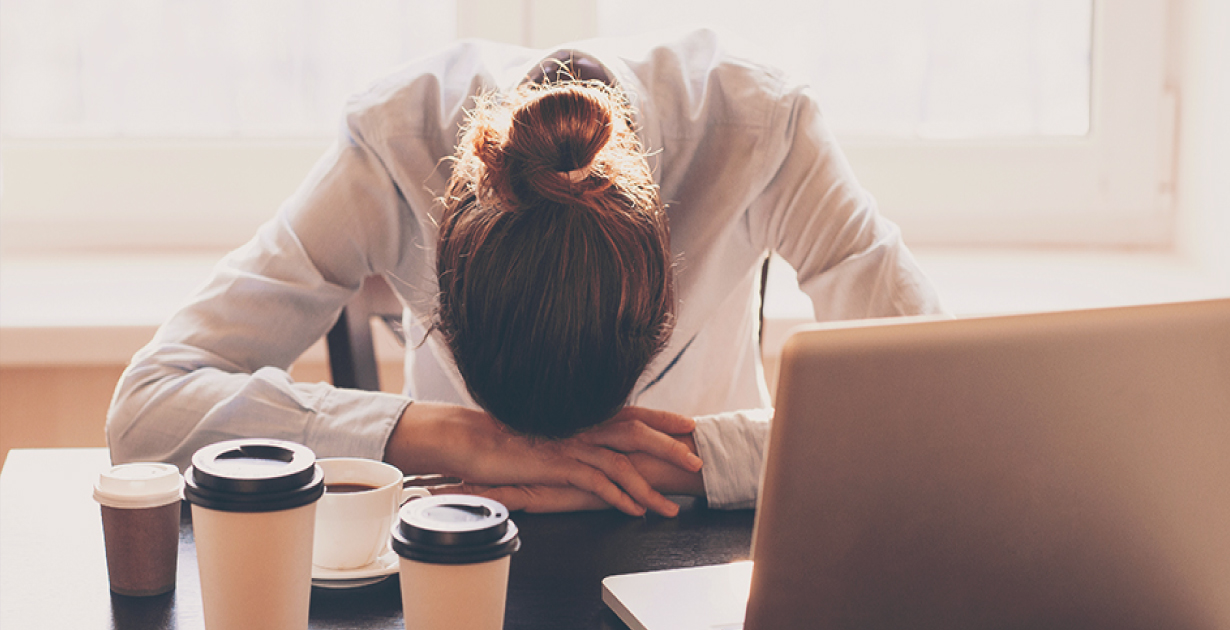 Woman lying with her head next to a cup of coffee on her office desk