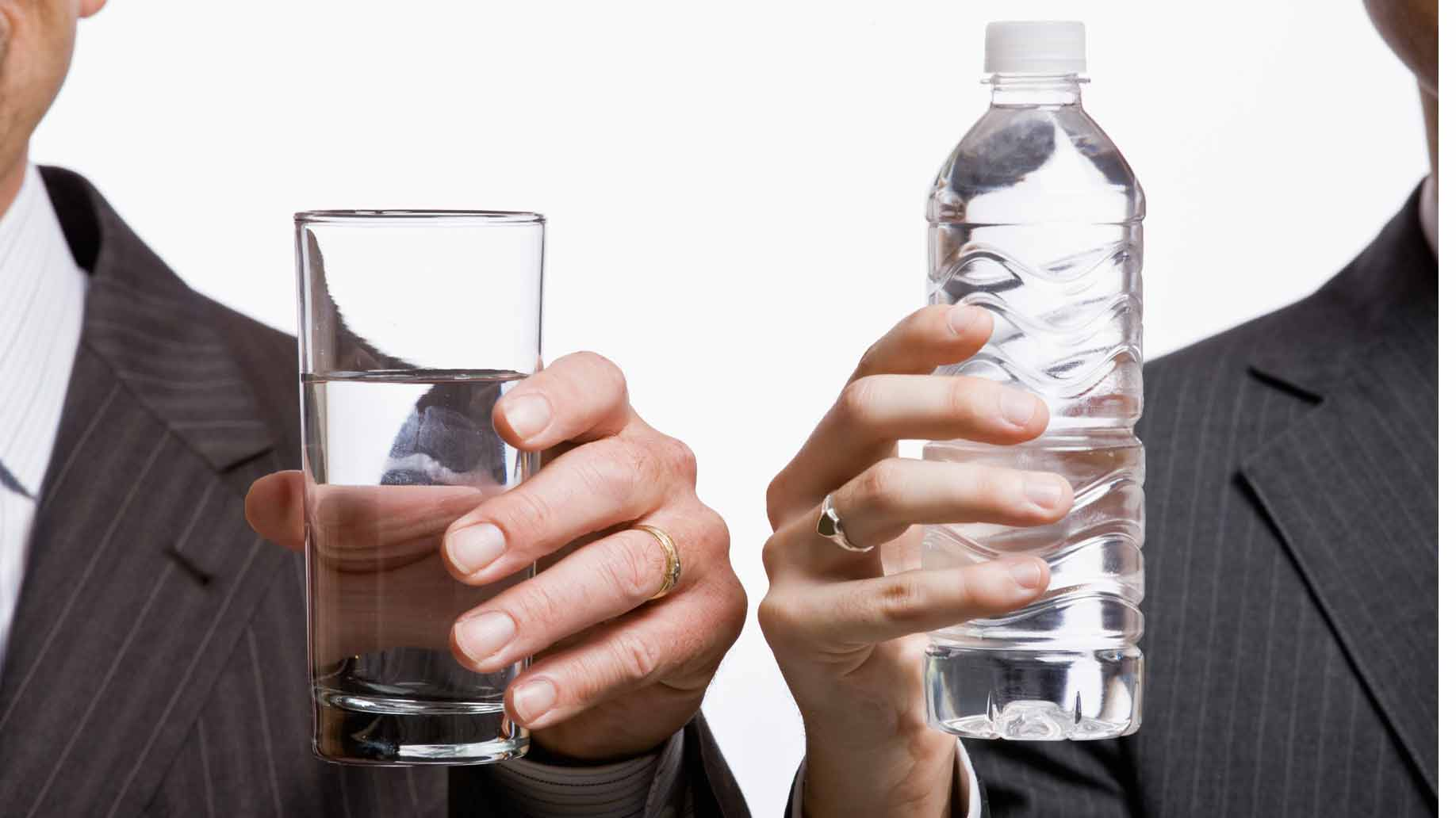 A hand holding a glass of water next to a hand holding a bottle of water
